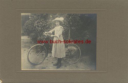 Mädchen mit Hut, ein Fahrrad schiebend (~1910)