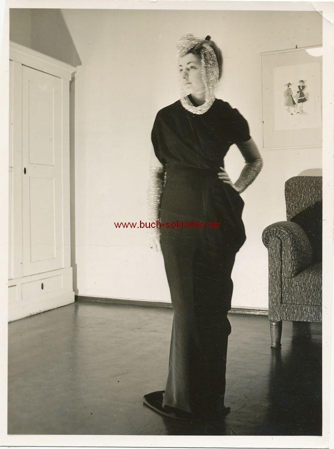 Foto Junge Frau im dunklen Kleid mit Stulpen, Hut u. Tuch (ca. 1950)