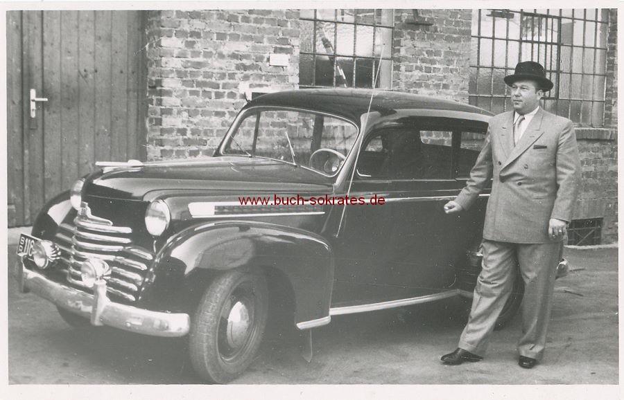 Foto Fabrik-Chef vor Oldtimer-Auto (wohl ein alter Opel Olympia) vor Tuchfabrik Theodor Ortmanns in Aachen-Brand, Eckenerstraße 31 (ca. 1950)