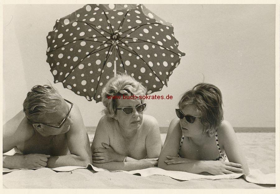 Foto Drei Personen am Strand mit Sonnenschirm (ca. 1960)