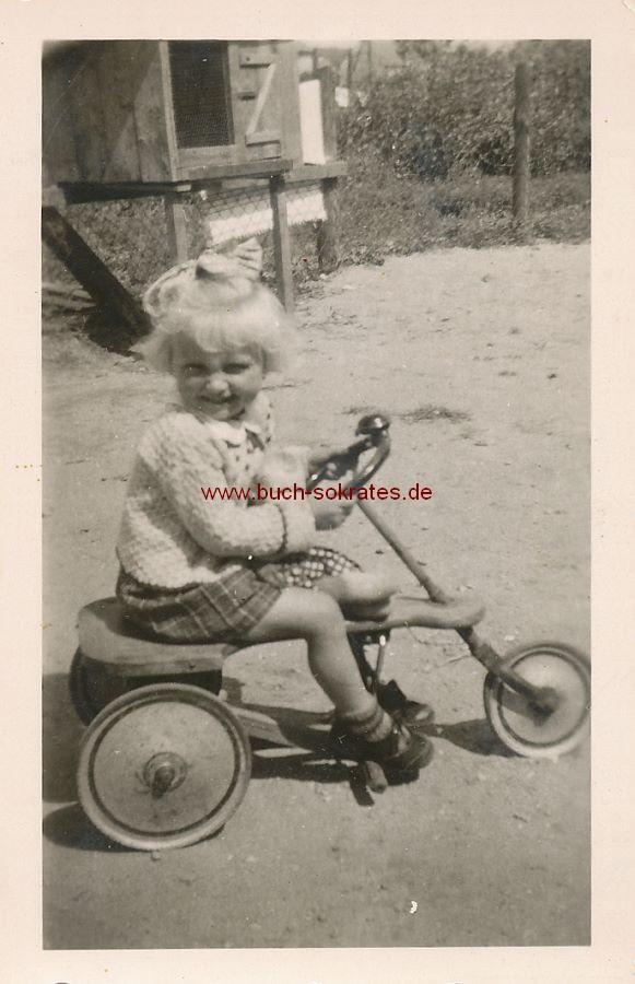 Foto Kleines Mädchen aus Mölln auf Dreirad mit Puppe (1943)