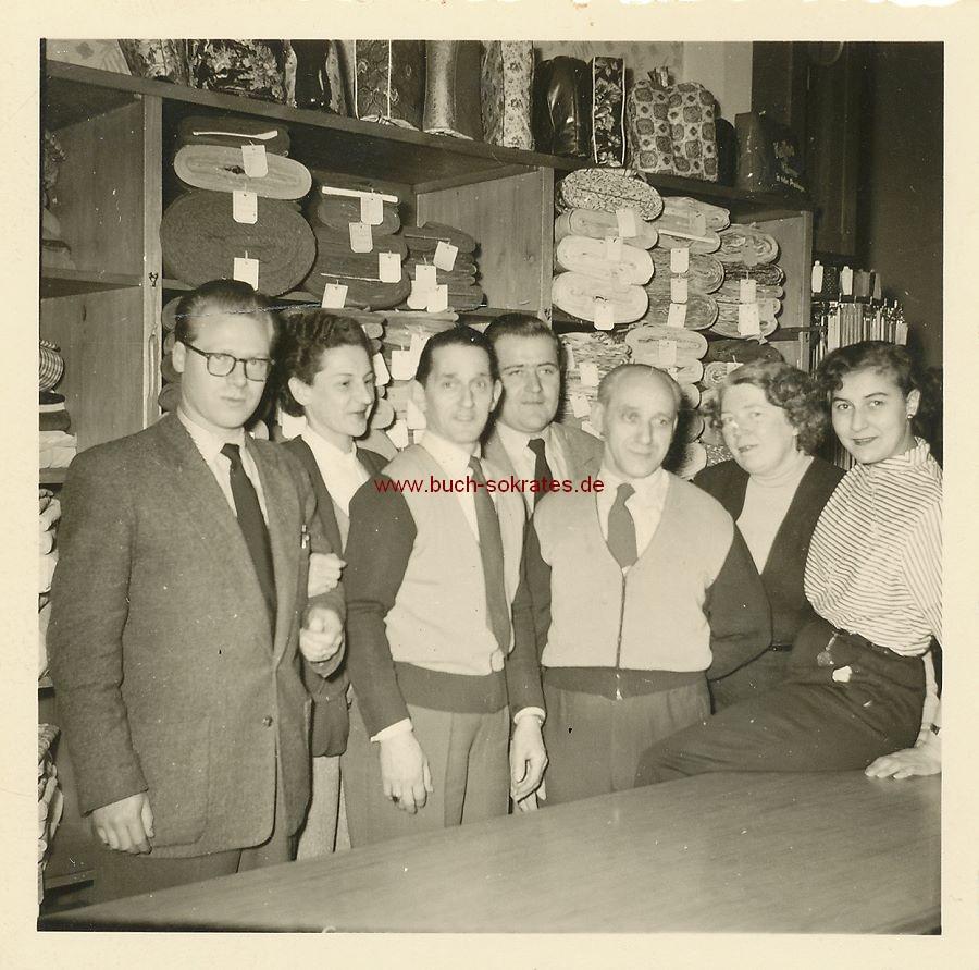 Foto Gruppenbild Angestellte / Verkäufer in einem Stoff-Laden hinter einem Tresen, vor Regalen mit Stoffbahnen (ca. 1935)