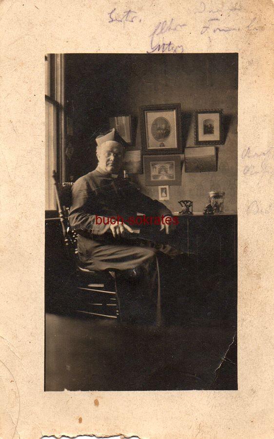 s/w-Foto-Postkarte Pfarrers aus Aachen in Amtstracht mit Mütze, auf einem Stuhl in einer Stube sitzend (1918)